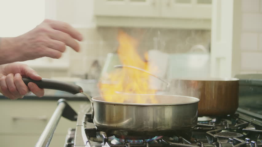 Man Cooking Food In Flambe Style At Kitchen