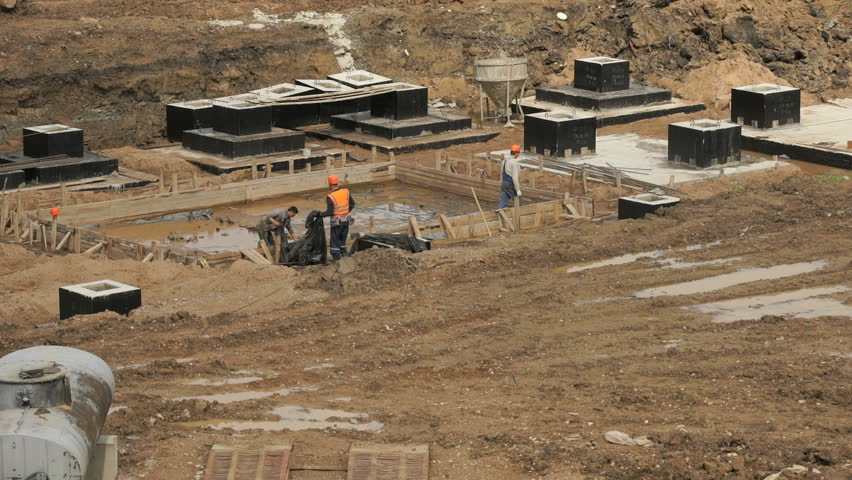 Large construction site. Workers in helmets and suits level surface and pour the foundation for building into wooden formwork outdoors