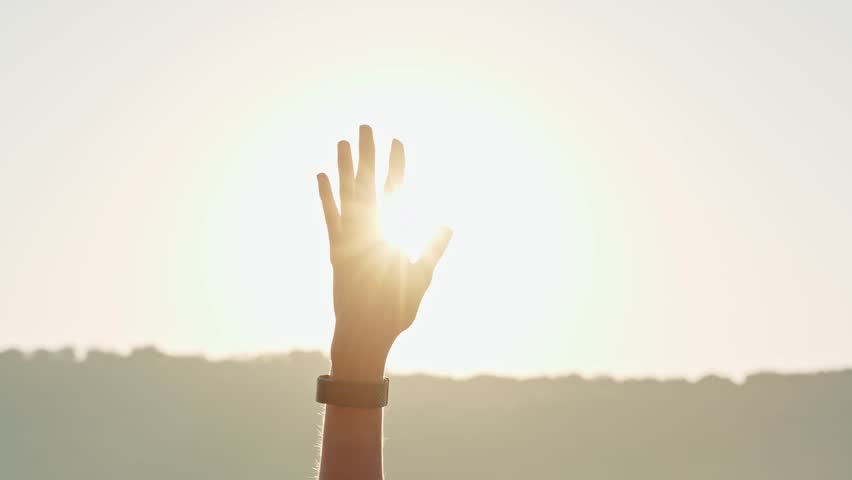Woman reaches hand up to sky at sunset | Shutterstock HD Video #1008924803