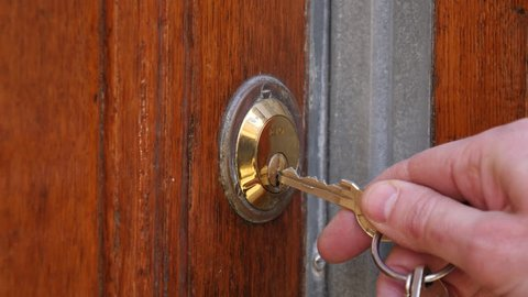 Using a key to open the lock of the front door.