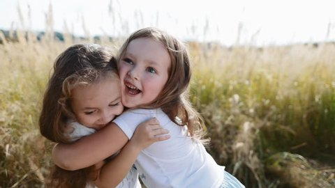 Two smiling, curly, cute baby-girls hug tightly each other. True friendship, friends for ages. Playing, happy childhood, positive emotions, true feelings