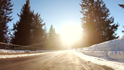 POV driving in the dazzling sun in a snowy winter forest