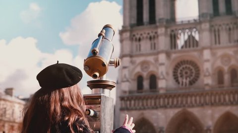 Little girl in beret looks through coin telescope. Slow motion. Notre-Dame de Paris. Child coming up, using tower viewer