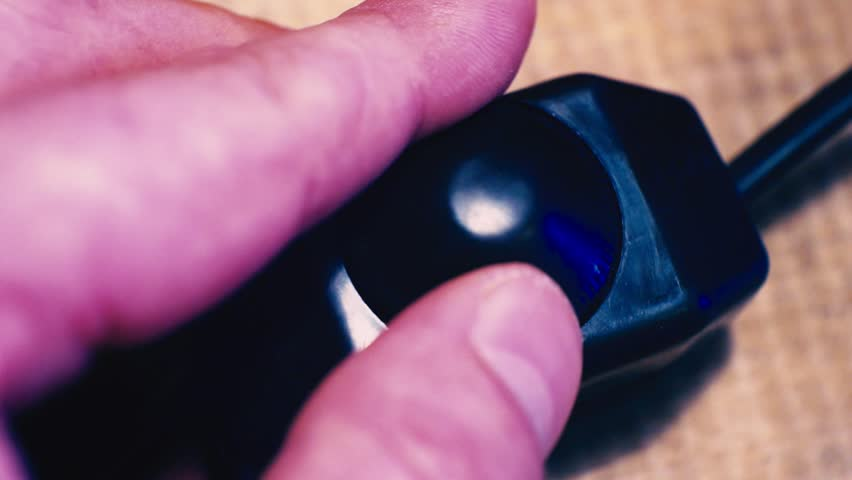 fingers twist the control wheel on the switch, which adjusts the brightness of the light.close-up.