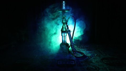 Hookah hot coals on shisha bowl making clouds of steam at Arabian interior. Oriental ornament on the carpet. Stylish oriental shisha in dark with backlight. Shisha on rotating display. Slider shot