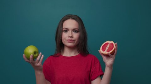 Attractive young woman on a dark green background chooses between apple and grapefruit, decides to bite the apple, than looks straight to camera and smiles.