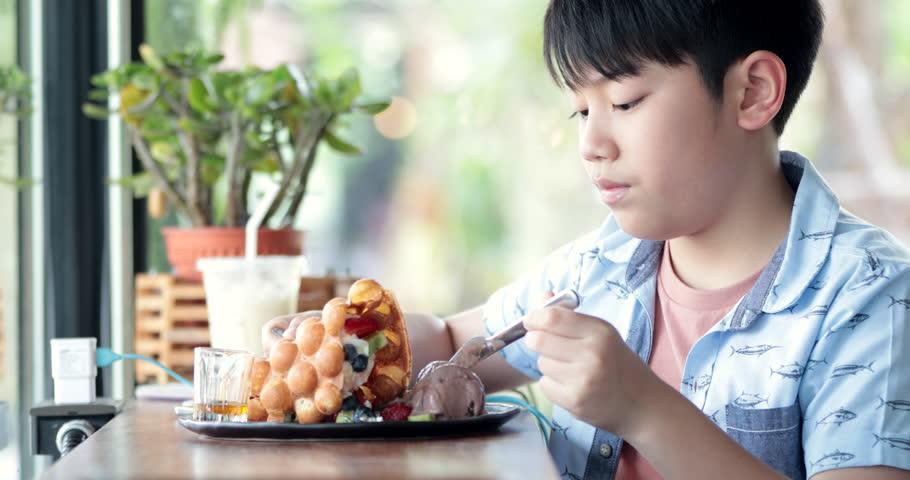 Asian boy enjoy eating Mix fruit with waffle.   Shutterstock HD Video #1008990773