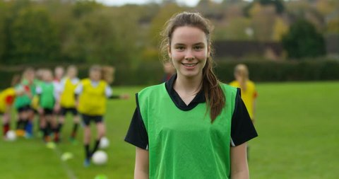 4K Portrait smiling British girl at soccer training, with team mates in the background. Slow motion.