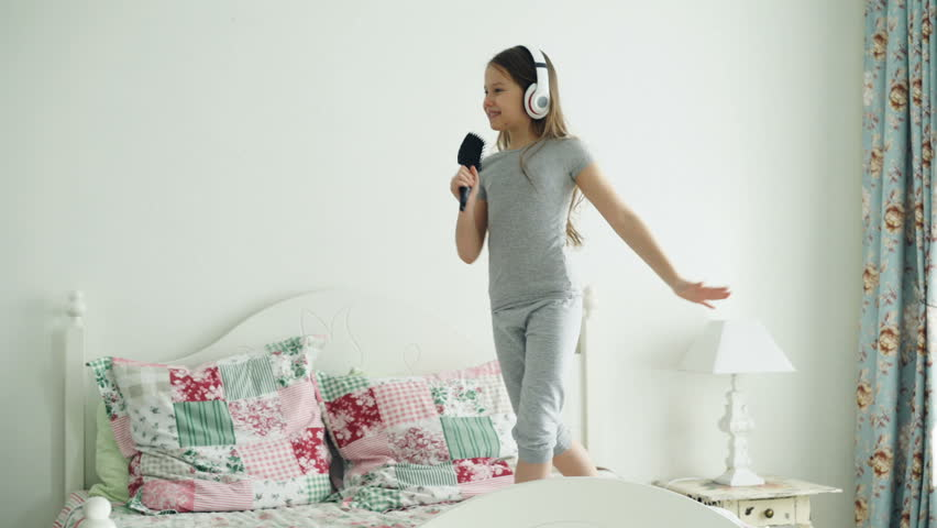 Funny cute little girl in wireless headphones dancing singing with comb and have fun on bed at home in cozy bedroom | Shutterstock HD Video #1009068713
