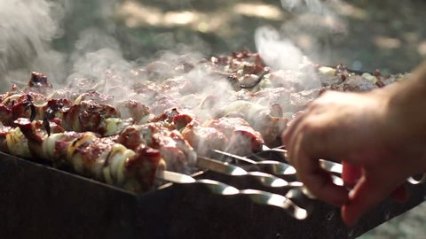 A man's hands rotating the skewers. Shish kebab. Pork or lamb meat pieces being fried on a charcoal grill. Frying grilled pieces of meat during the rest.