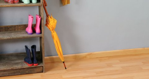 Umbrella, jumper and wellington boots on shoe rack against wall 4k