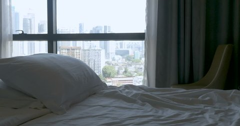 Tilt up of an empty bed with two pillows and a large city view and open curtains