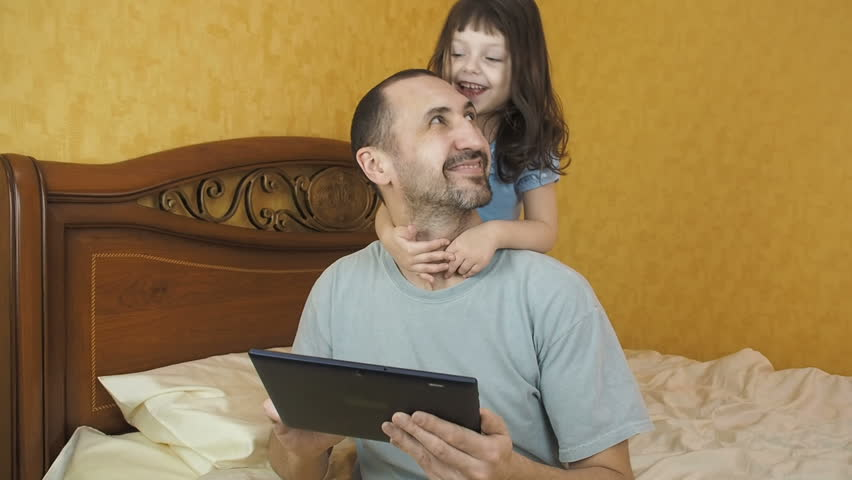 Father with a gadget. A child is hugging his father. | Shutterstock HD Video #1009124633