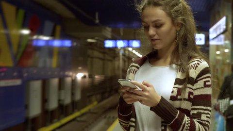 Woman using mobile phone at subway