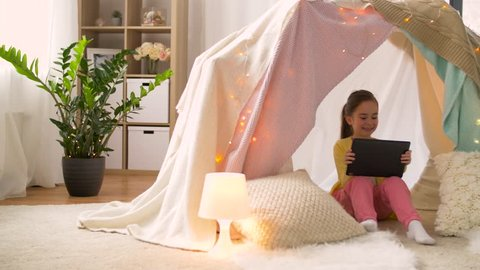 childhood, technology and hygge concept - happy little girl with tablet pc computer in kids tent at home