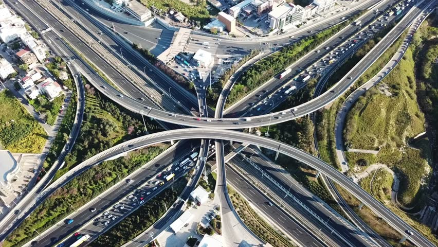 Aerial drone bird's eye view video of highway multilevel junction road, passing through city center