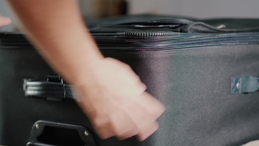 A man zips up a zipped bolt on the suitcase, takes it away. Eviction from the hotel and business trip concept