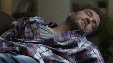 Untidy alcoholic sleeping on couch after home party, wasted man scratching belly