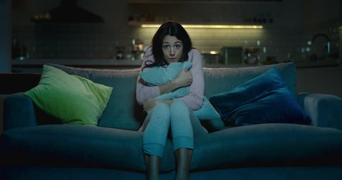 Frightened woman sitting on a sofa at night struggling to watch a scary movie on her own.