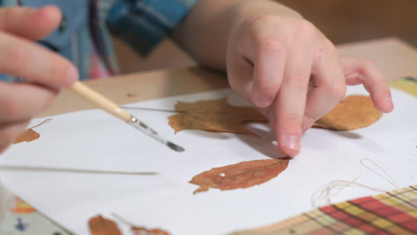 Unknown little child sitting on the table glues dry leaves on a white sheet. Beautiful herbarium from leaves of tree. Manual work. Child development in kindergarten | Shutterstock HD Video #1009175993