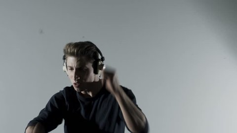 Young man listening to music through headphones and playing the air drums wildly in a studio. Medium shot.