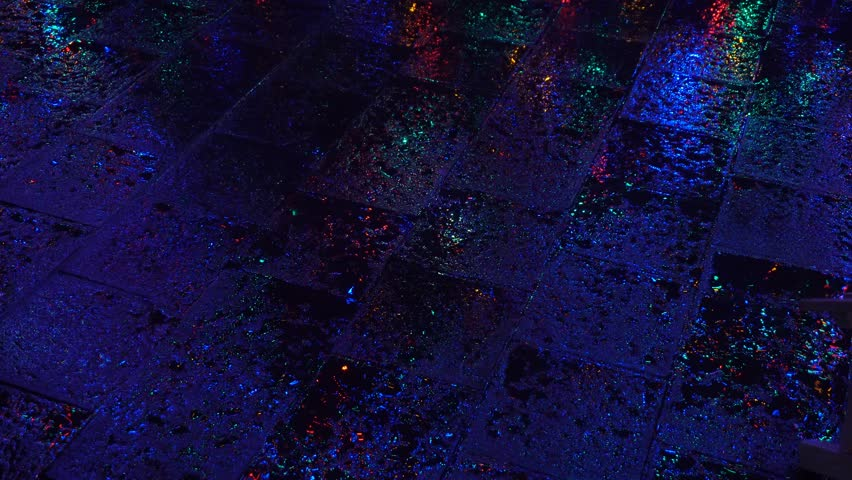 Rain drops on asphalt by night with lights
