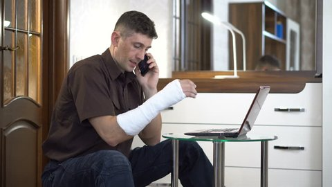 A man with a broken right hand in a plaster sits near a coffee table with a laptop and talks through a smartphone in a room with furniture. Broken arm