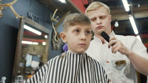 Professional barber doing a new haircut with the help of ridge and electric shaver. Beautiful boy and stylist or hairdresser with trimmer doing haircut at hair salon or barber shop, 4k