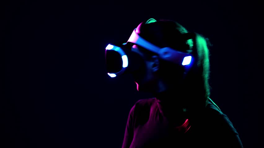 Young woman in VR headset looks around and wonders how amazing. Virtual reality helmet on black background