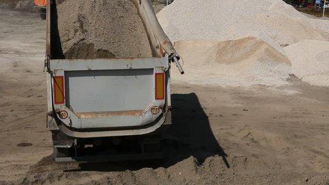 Dumper truck is unload soil. Dumper truck is unloading sand in excavator range at construction site.