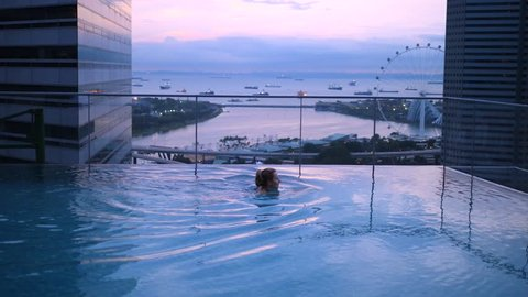 Young Tourist Woman Swimming In Rooftop Pool At Sunrise On Holiday