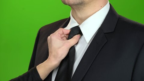Woman's hand adjusts the tie around her servant's neck. Green screen. Close up