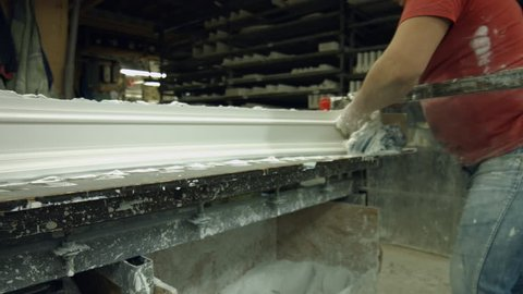 Gypsum shaping in workshop. Manufacturing of cornice by skillful specialist. Production of expensive cornices at manufacture.
