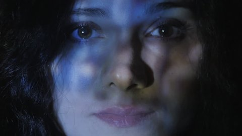 Close up portrait of a young woman watching a video or film on TV or a computer monitor. Reflection on her face