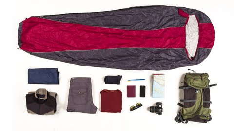 Top view on sleeping bag packing with travelers equipment on white background. 4k stop motion animation.