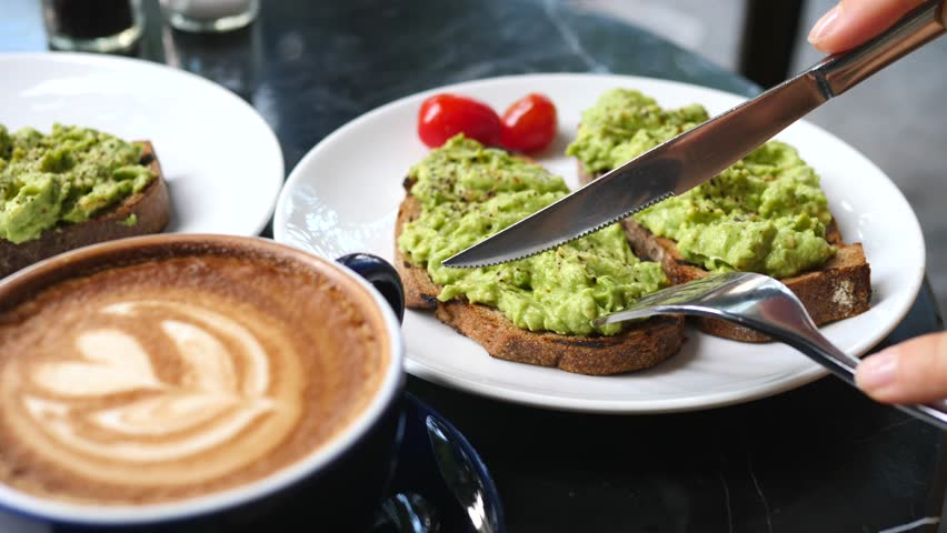 Close Up Of Female Hands Cutting Avocado Toast While Having Breakfast With Coffee
