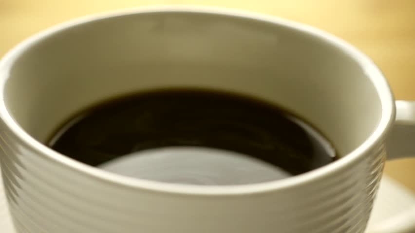pouring stream milk into a cup of espresso in slow motion #1009286573