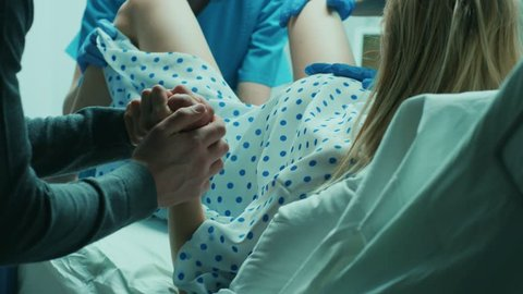In the Hospital Woman Giving Birth, Husband Holds Her Hand in Support, Obstetricians Assisting. Modern Delivery Ward with Professional Midwives. Shot on RED EPIC-W 8K Helium Cinema Camera.