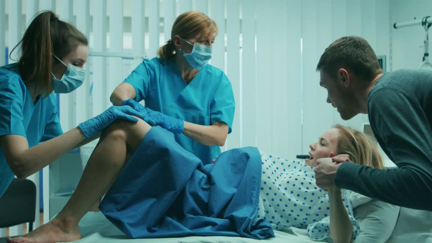 In the Hospital Woman in Labor Pushes to Give Birth, Obstetricians Assisting, Husband Holds Her Hand. Modern Delivery Ward with Professional Midwives. Shot on RED EPIC-W 8K Helium Cinema Camera. | Shutterstock HD Video #1009293713