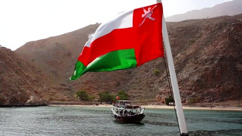 Oman flag back of a boat on sea. Musandam peninsula, Sultanate of Oman, Gulf of Oman