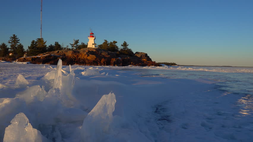 Pan view of dramatic ice formation along the rocky shoreline of Georgian Bay with Killarney historical lighthouse, built in 1850s, in background