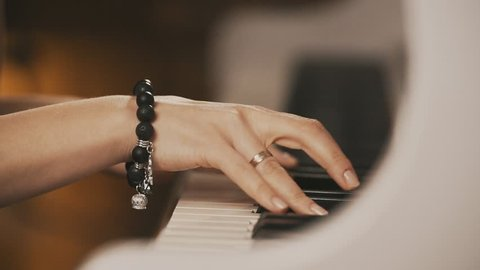 Female hands playing piano. Female hands with bracelet on piano. Woman touches fingers on keys. Close up.