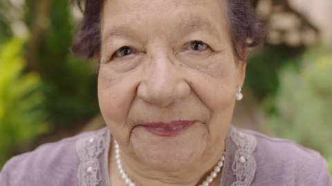 close up portrait of pretty elderly woman looking smiling pensive at camera wearing pearl necklace