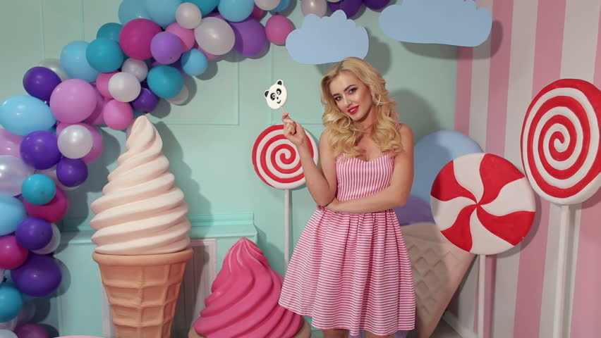 Portrait of a Barbie girl with blond curly hair in a pink dress and a big candy in her hands at a candy party.
