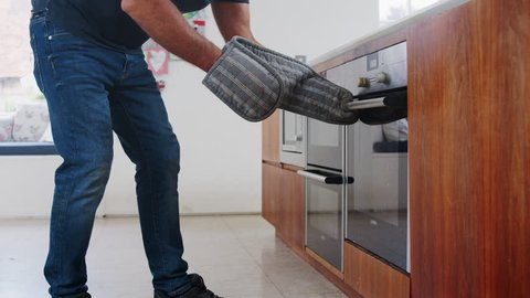 Mature Man In Kitchen Takes Burning Meal Out Of Oven