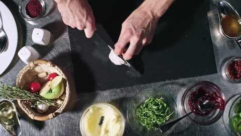 Top view of unrecognizable cook cutting garlic cloves on tabletop in kitchen