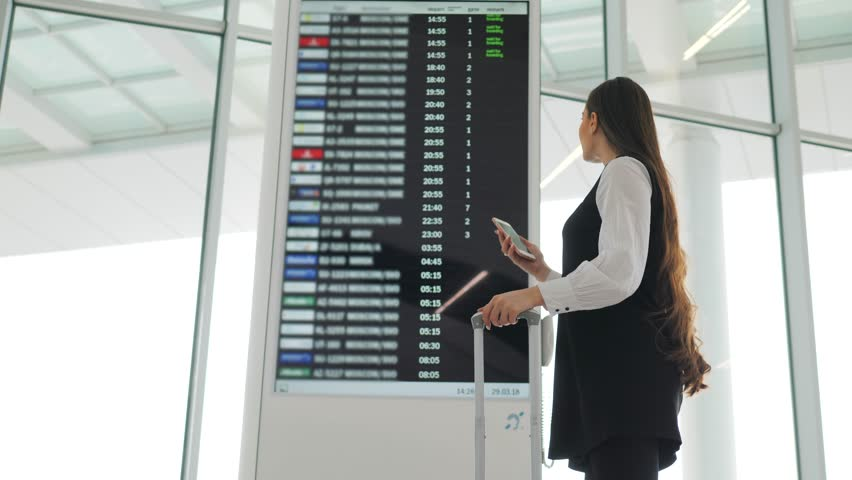 Travel woman using smartphone at airport. Young caucasian traveler checking boarding time with mobile phone app in terminal or train station. Business woman businesswoman Tourist on vacation
