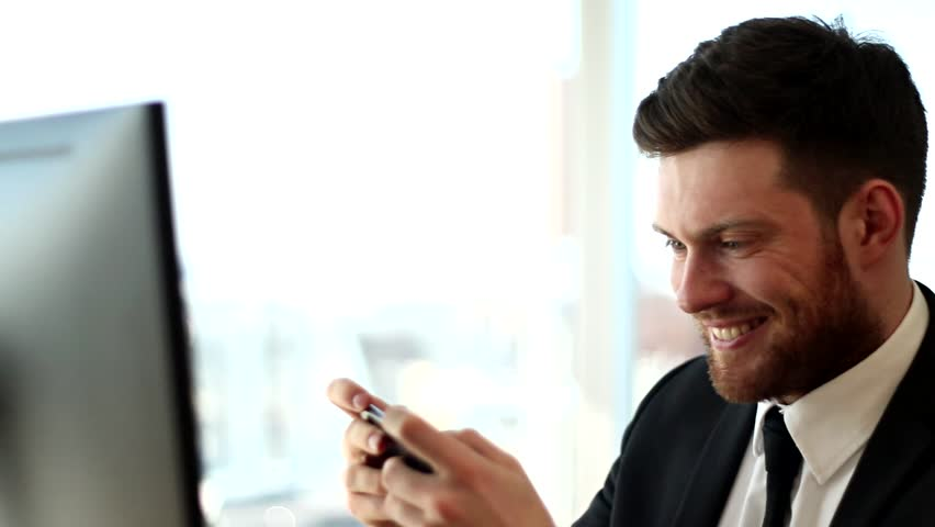 Businessman is playing phone games at office. He has done all work and relaxing. Happy businessman.