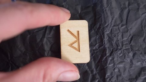 rune. close-up, hand puts the rune on the surface for divination. 4k, slow-motion