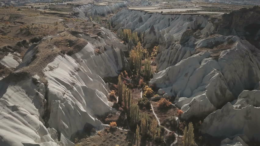 Forward advancing aerial drone high angle view fly-over and winding thru Love Valley trekking trail with natural Cappadocia fairy chimney landscape in Goreme, Turkey. Pt 2 of 3. 4k at 29.97fps